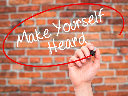 heard: Man Hand writing Make Yourself Heard with black marker on visual screen. Isolated on background. Business, technology, internet concept. Stock Photo