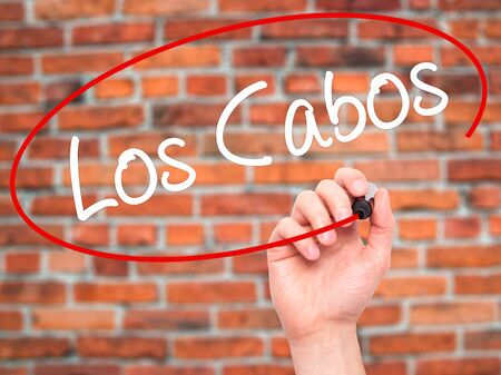 los cabos: Man Hand writing Los Cabos with black marker on visual screen. Isolated on bricks. Business, technology, internet concept. Stock Photo