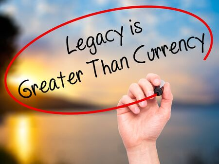 Man Hand writing Legacy is Greater Than Currency with black marker on visual screen. Isolated on background. Business, technology, internet concept. Stock Photo