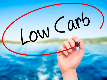 carb: Man Hand writing Low Carb with black marker on visual screen. Isolated on nature. Business, technology, internet concept. Stock Photo