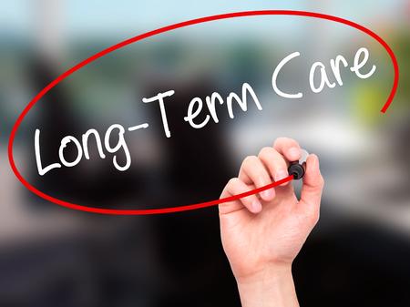 pflegeversicherung: Man Hand schreiben Langzeitpflege mit schwarzen Marker auf visuellen Bildschirm. Isoliert auf B�ro. Wirtschaft, Technik, Internet-Konzept. Stockfoto