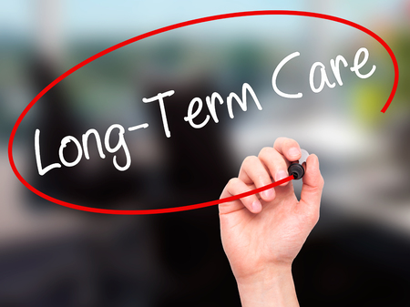 ltc: Man Hand writing Long-Term Care with black marker on visual screen. Isolated on office. Business, technology, internet concept. Stock Photo Stock Photo