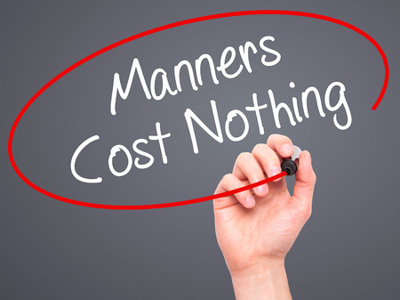 bad manners: Man Hand writing Manners Cost Nothing with black marker on visual screen. Isolated on grey. Business, technology, internet concept. Stock Photo Stock Photo