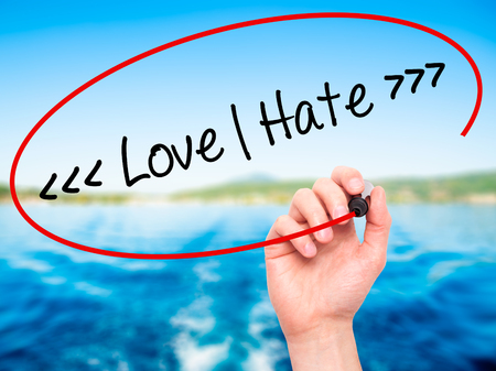 appraise: Man Hand writing Love - Hate  with black marker on visual screen. Isolated on background. Business, technology, internet concept. Stock Photo