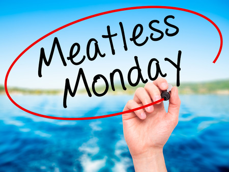 meatless: Man Hand writing Meatless Monday with black marker on visual screen. Isolated on nature. Life, technology, internet concept. Stock Image Stock Photo