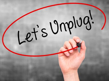 unplug: Man Hand writing Lets Unplug! with black marker on visual screen. Isolated on grey. Business, technology, internet concept. Stock Photo