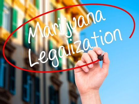 oppose: Man Hand writing Marijuana Legalization with black marker on visual screen. Isolated on city. Live, technology, internet concept. Stock Photo Stock Photo