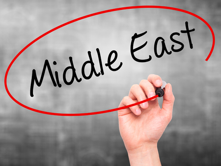 ksa: Man Hand writing Middle East with black marker on visual screen. Isolated on grey. Business, technology, internet concept. Stock Photo