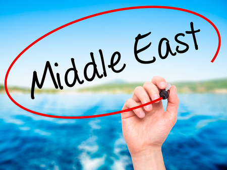 ksa: Man Hand writing Middle East with black marker on visual screen. Isolated on nature. Business, technology, internet concept. Stock Photo Stock Photo