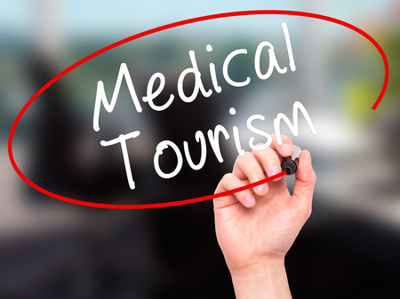 health care fees: Man Hand writing Medical Tourism with black marker on visual screen. Isolated on office. Business, technology, internet concept. Stock Photo