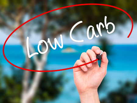 nonfat: Man Hand writing Low Carb with black marker on visual screen. Isolated on nature. Business, technology, internet concept. Stock Photo