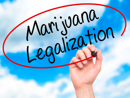 legislators: Man Hand writing Marijuana Legalization with black marker on visual screen. Isolated on sky. Live, technology, internet concept. Stock Photo
