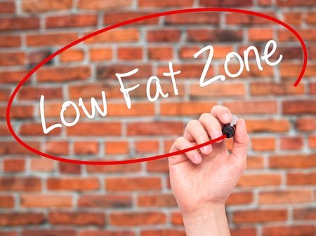 low fat: Man Hand writing Low Fat Zone with black marker on visual screen. Isolated on bricks. Business, technology, internet concept. Stock Photo