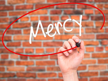 personal god: Man Hand writing Mercy with black marker on visual screen. Isolated on bricks. Business, technology, internet concept. Stock Photo