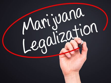 legislators: Man Hand writing Marijuana Legalization with black marker on visual screen. Isolated on black. Live, technology, internet concept. Stock Photo Stock Photo