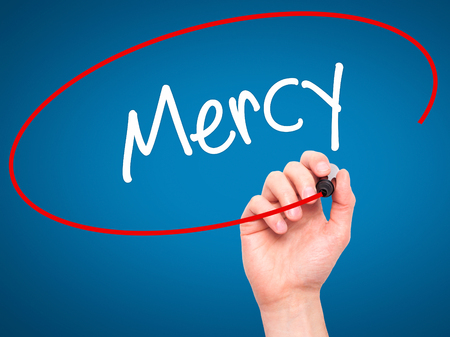 personal god: Man Hand writing Mercy with black marker on visual screen. Isolated on blue. Business, technology, internet concept. Stock Photo