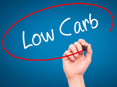 carb: Man Hand writing Low Carb with black marker on visual screen. Isolated on blue. Business, technology, internet concept. Stock Photo
