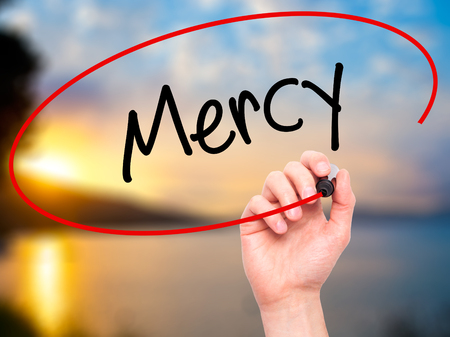 personal god: Man Hand writing Mercy with black marker on visual screen. Isolated on nature. Business, technology, internet concept. Stock Photo