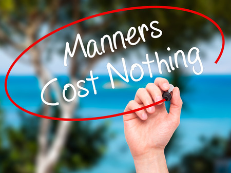 bad manners: Man Hand writing Manners Cost Nothing with black marker on visual screen. Isolated on nature. Business, technology, internet concept. Stock Photo