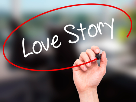 photo story: Man Hand writing Love Story with black marker on visual screen. Isolated on office. Business, technology, internet concept. Stock Photo