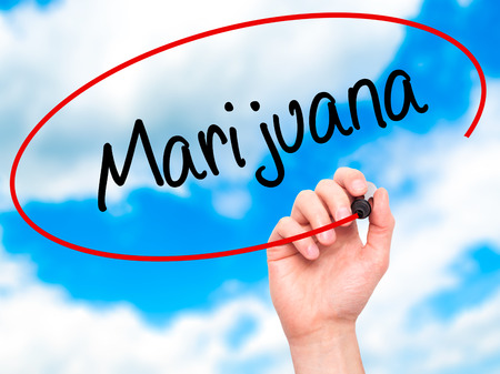 american downloads: Man Hand writing Marijuana with black marker on visual screen. Isolated on sky. Business, technology, internet concept. Stock Photo