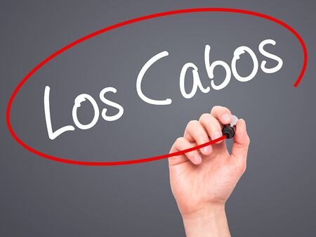 los cabos: Man Hand writing Los Cabos with black marker on visual screen. Isolated on grey. Business, technology, internet concept. Stock Photo