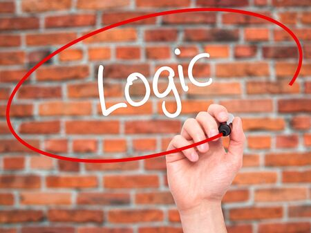 algebraic: Man Hand writing Logic with black marker on visual screen. Isolated on bricks. Business, technology, internet concept.