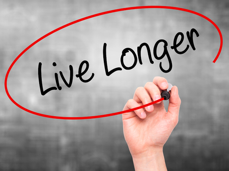 longer: Man Hand writing Live Longer with black marker on visual screen. Isolated on grey. Business, technology, internet concept. Stock Photo