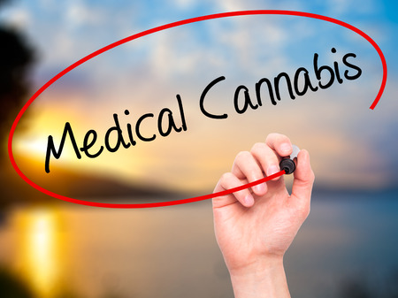 legalization: Man Hand writing Medical Cannabis with black marker on visual screen. Isolated on background. Business, technology, internet concept. Stock Photo