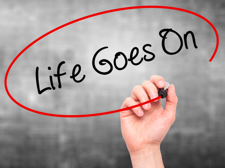 Man Hand writing Life Goes On with black marker on visual screen. Isolated on grey. Business, technology, internet concept. Stock Photo
