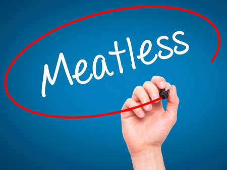 meatless: Man Hand writing Meatless  with black marker on visual screen. Isolated on blue. Business, technology, internet concept. Stock Photo