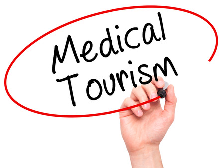 health care fees: Man Hand writing Medical Tourism with black marker on visual screen. Isolated on white. Business, technology, internet concept. Stock Photo Stock Photo
