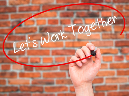 combined effort: Man Hand writing Lets Work Together with black marker on visual screen. Isolated on background. Business, technology, internet concept. Stock Photo