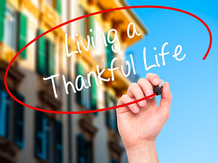 acknowledgment: Man Hand writing Living a Thankful Life with black marker on visual screen. Isolated on city. Business, technology, internet concept.
