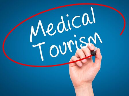 health care fees: Man Hand writing Medical Tourism with black marker on visual screen. Isolated on blue. Business, technology, internet concept. Stock Photo