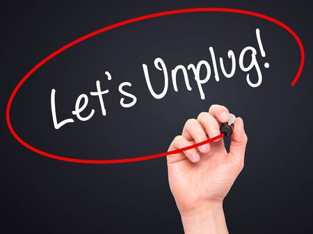 unplug: Man Hand writing Lets Unplug! with black marker on visual screen. Isolated on black. Business, technology, internet concept. Stock Photo Stock Photo
