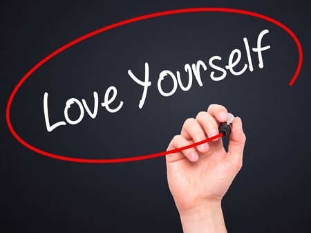 egoistic: Man Hand writing Love Yourself with black marker on visual screen. Isolated on black. Business, technology, internet concept. Stock Photo