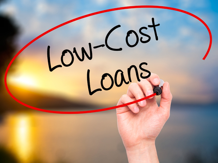 unemployment rate: Man Hand writing Low-Cost Loans with black marker on visual screen. Isolated on background. Business, technology, internet concept. Stock Photo