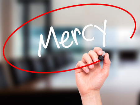 Man Hand writing Mercy with black marker on visual screen. Isolated on office. Business, technology, internet concept. Stock Photo