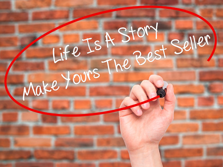 photo story: Man Hand writing Life Is A Story Make Yours The Best Seller with black marker on visual screen. Isolated on background. Business, technology, internet concept. Stock Photo