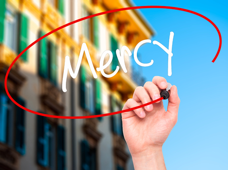 personal god: Man Hand writing Mercy with black marker on visual screen. Isolated on city. Business, technology, internet concept. Stock Photo