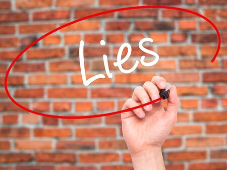 no integrity: Man Hand writing Lies with black marker on visual screen. Isolated on bricks. Business, technology, internet concept. Stock Photo