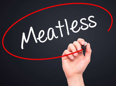 meatless: Man Hand writing Meatless  with black marker on visual screen. Isolated on black. Business, technology, internet concept. Stock Photo Stock Photo