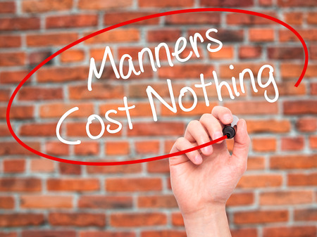 manners: Man Hand writing Manners Cost Nothing with black marker on visual screen. Isolated on bricks. Business, technology, internet concept. Stock Photo