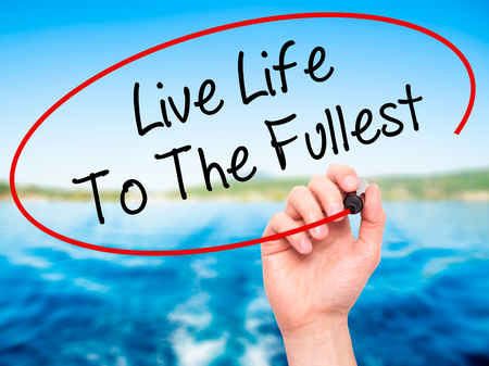 love life: Man Hand writing Live Life To The Fullest with black marker on visual screen. Isolated on background. Business, technology, internet concept. Stock Photo