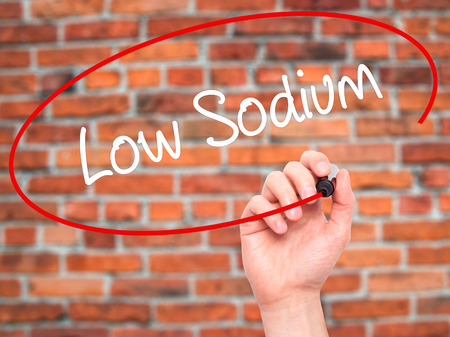 Man Hand writing Low Sodium with black marker on visual screen. Isolated on background. Business, technology, internet concept. Stock Photo Stock Photo