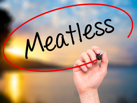 meatless: Man Hand writing Meatless  with black marker on visual screen. Isolated on nature. Business, technology, internet concept. Stock Photo