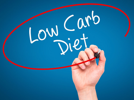 low carb diet: Man Hand writing Low Carb Diet with black marker on visual screen. Isolated on blue. Business, technology, internet concept. Stock Photo