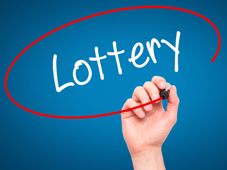 lottery win: Man Hand writing Lottery  with black marker on visual screen. Isolated on blue. Business, technology, internet concept. Stock Photo Stock Photo