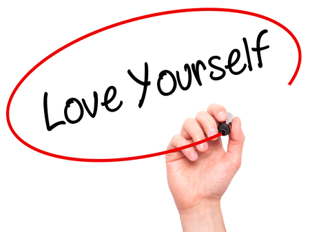 egoistic: Man Hand writing Love Yourself with black marker on visual screen. Isolated on white. Business, technology, internet concept. Stock Photo